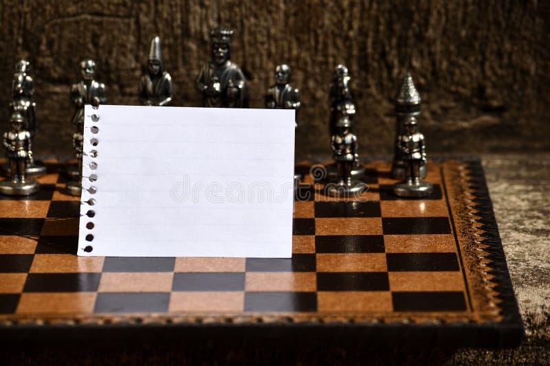 Espiral limpa vazia - folha ordenada encadernada do caderno rasgada fora e dobrada ao meio colocado no tabuleiro de xadrez na fre imagens de stock royalty free