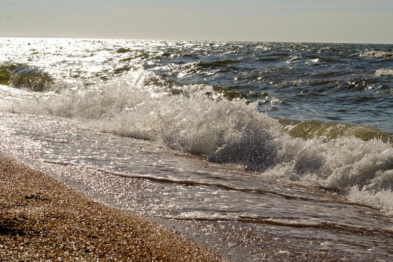 Espirra das ondas na praia da costa de mar em um dia ensolarado brilhante foto de stock royalty free