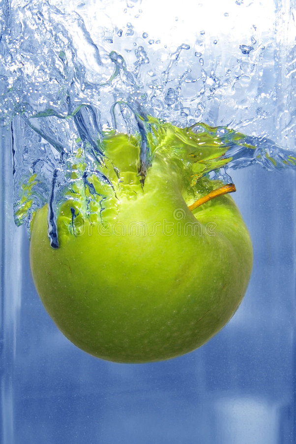 Espirrando a maçã em uma água fotos de stock royalty free
