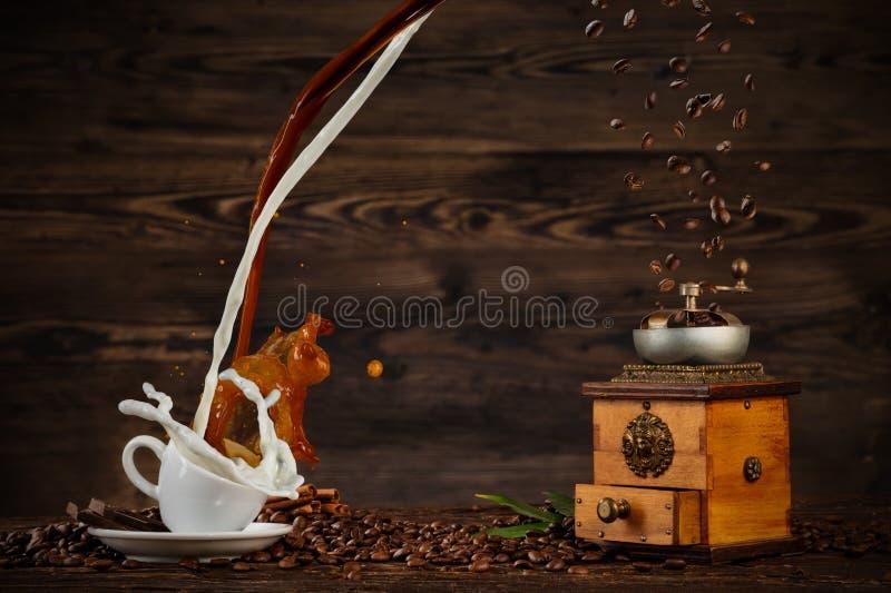 Espirrando o líquido do café e do leite no copo branco na tabela de madeira fotos de stock royalty free