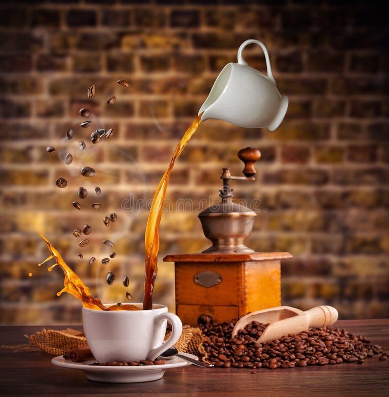 Espirrando o líquido do café no copo branco na tabela de madeira imagem de stock royalty free