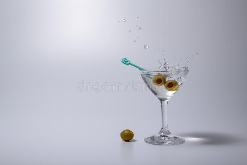 Espirrando o licor do cocktail de Martini beba com a azeitona conservada fotografia de stock royalty free