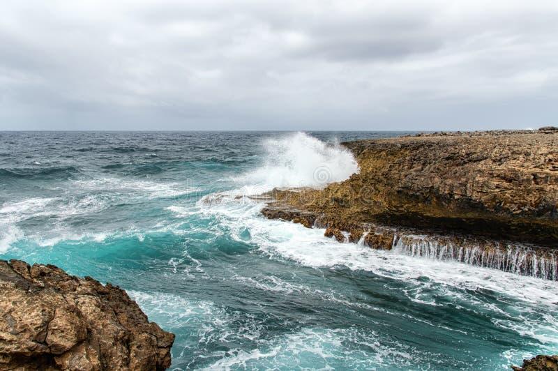 Espirrar acena em um litoral áspero e rochoso fotos de stock royalty free