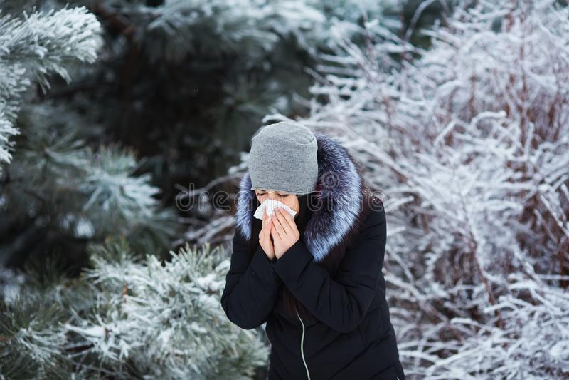 Espirrar fêmea A jovem mulher bonita tem a gripe e a febre no dia de inverno exterior foto de stock