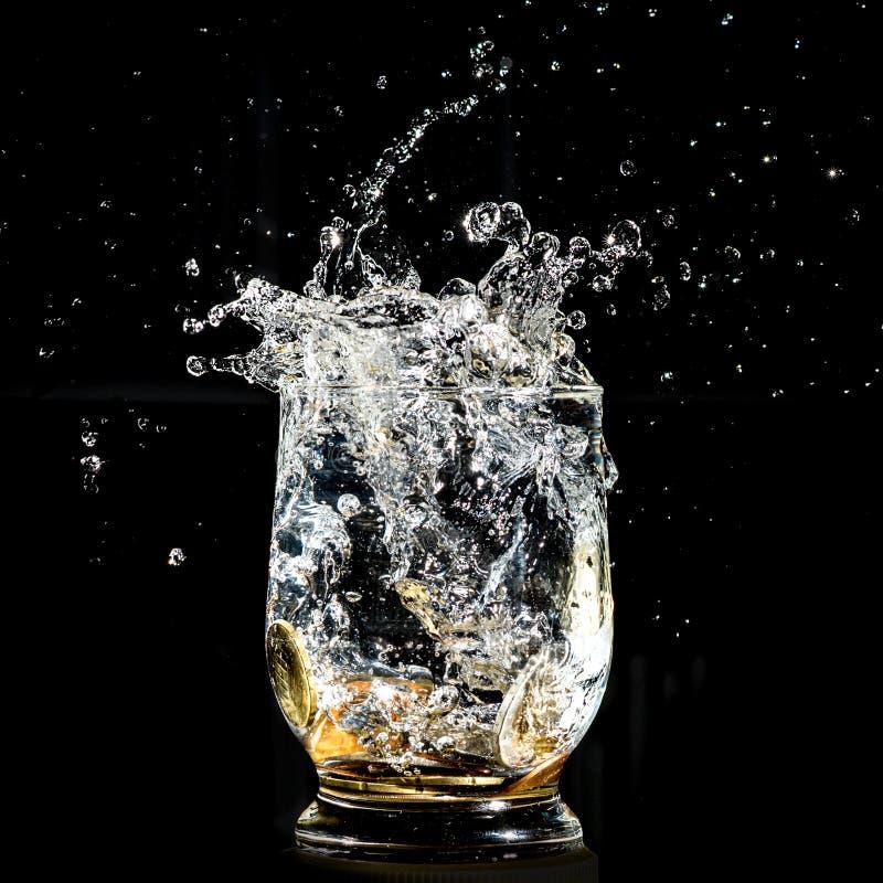Espirro de queda das moedas em um vidro de água fotografia de stock