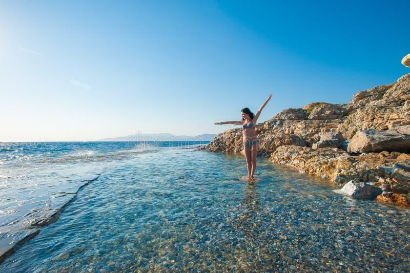 Espirro do mar na menina mulher que joga na água do oceano foto de stock