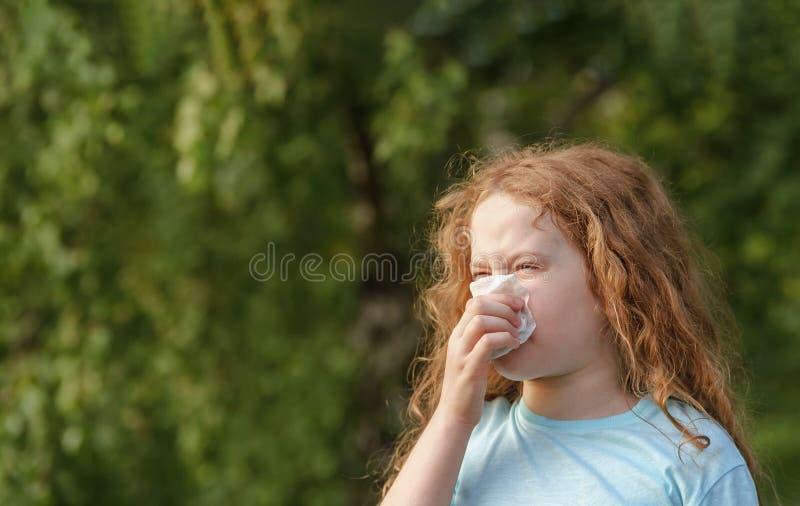 Espirro doente da menina no len?o no ar livre imagens de stock royalty free