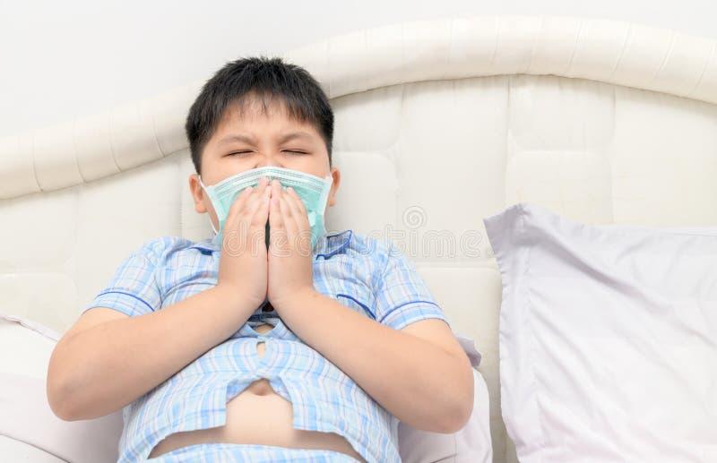 Espirro gordo obeso asiático do menino com proteção da máscara protetora foto de stock