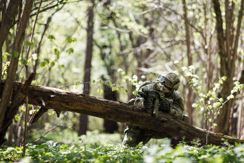 Esploratore con le armi in foresta fotografie stock