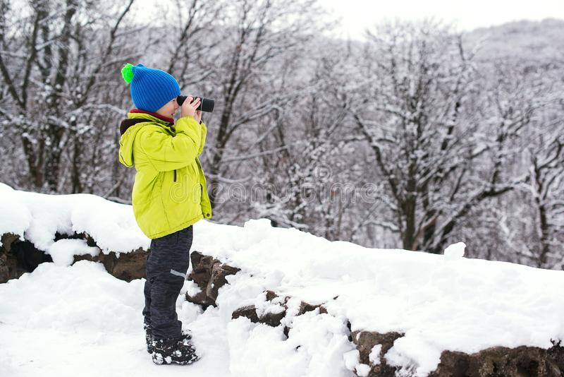 Esploratore della natura del bambino di ?ute nell'esploratore del binocolo del ragazzino della foresta di inverno alla natura di  fotografia stock libera da diritti