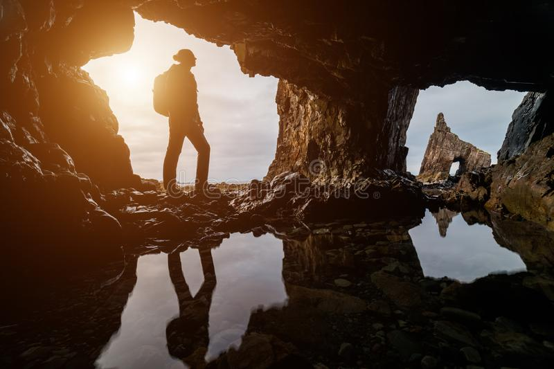 Esploratore in una caverna al tramonto in spiaggia di Portizuelo, costa delle Asturie, Spagna del nord fotografie stock