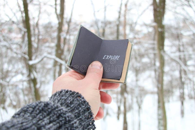 Esplorazione concetto Mano con la scritta sullo sfondo della foresta invernale fotografie stock libere da diritti