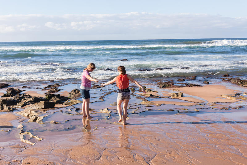 Esplorazione delle onde della spiaggia della figlia della madre immagini stock
