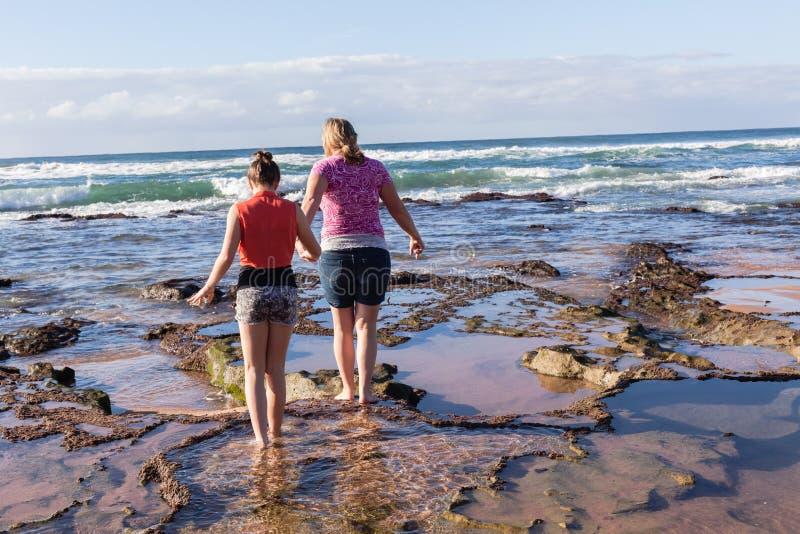 Esplorazione delle onde della spiaggia della figlia della madre immagine stock