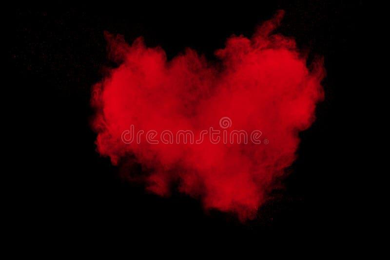 Esplosione astratta di polvere rossa su fondo nero Cuore rosso immagini stock