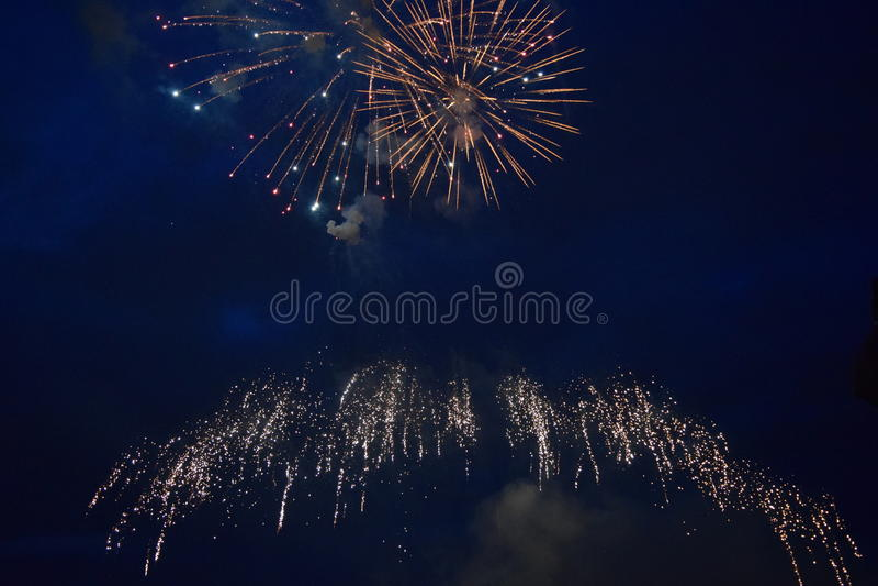 Esplosioni dei fuochi d'artificio nel cielo notturno immagini stock