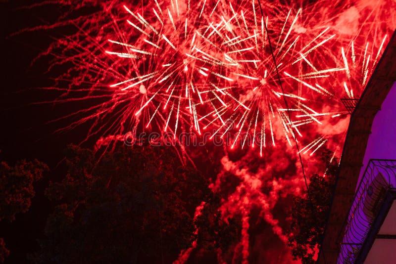 Esplosioni dei fuochi d'artificio rossi sui precedenti su un balcone scuro dell'hotel e del cielo notturno immagine stock