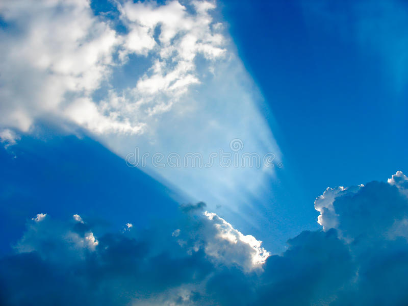Esponga al sole colpire attraverso le nuvole come un proiettore immagini stock