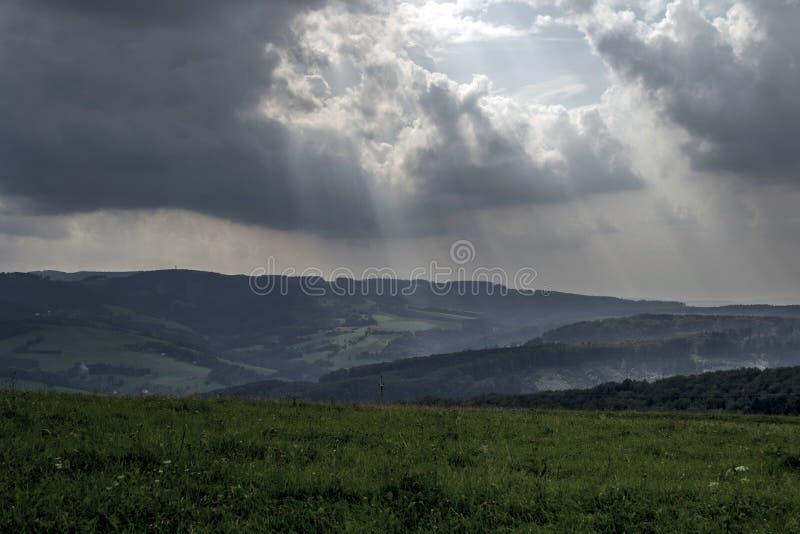 Esponga al sole i raggi dalle nuvole di tempesta sulle colline verdi nei prati fotografia stock