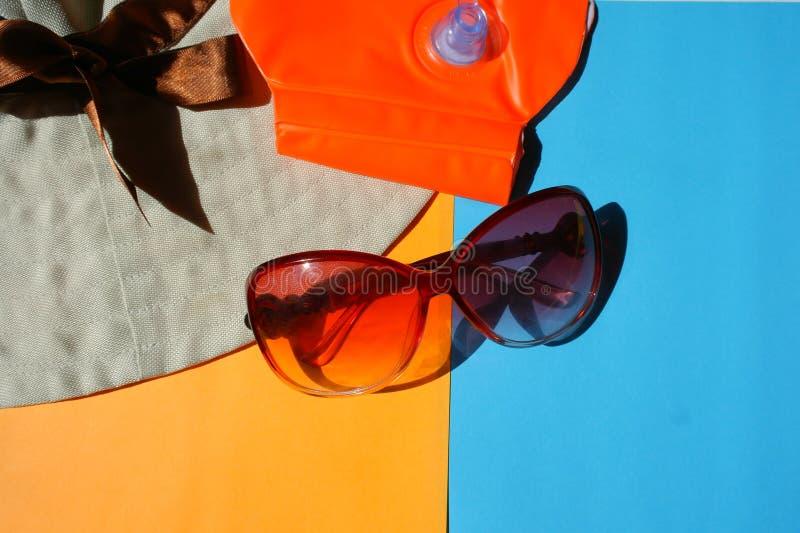 Esponga al sole i vetri di protezione, cappello su fondo blu ed arancio fotografie stock libere da diritti