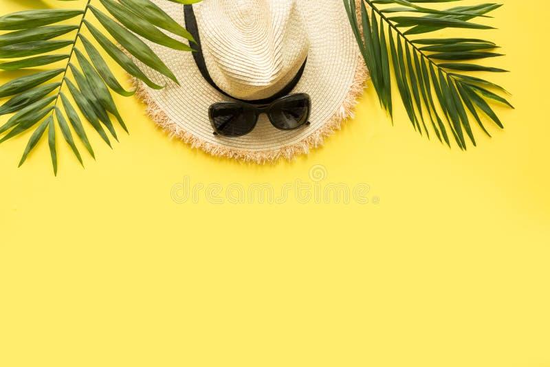 Esponga al sole il cappello della spiaggia della paglia con gli occhiali e la palma tropicale su giallo Concetto di vacanze estiv immagine stock