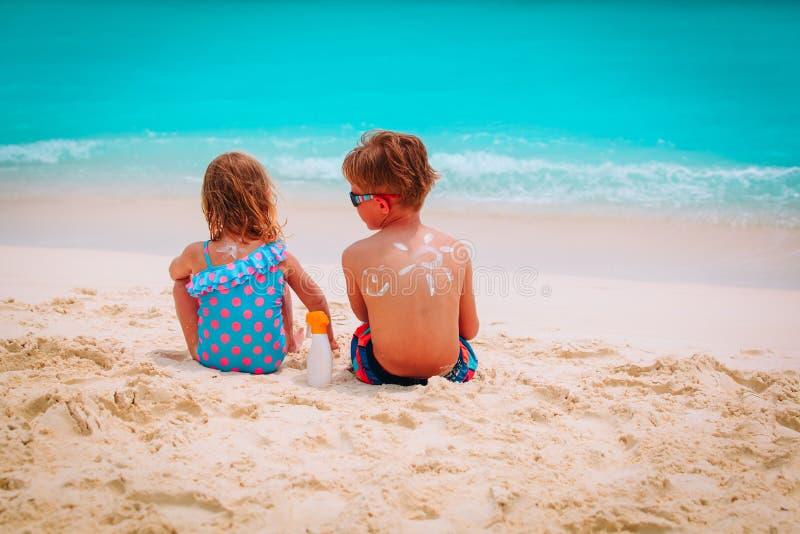 Esponga al sole il ragazzino e la ragazza della protezione con suncream alla spiaggia immagini stock