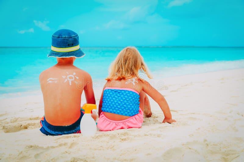 Esponga al sole il ragazzino e la ragazza della protezione con suncream alla spiaggia immagine stock libera da diritti