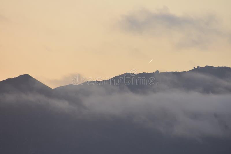 Esponga al sole la regolazione con l'aumento della nebbia e un passaggio della cometa fotografie stock