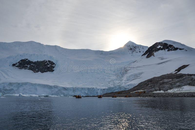 Esponga al sole la regolazione su una montagna dell'Antartide con le barche dello zodiaco nei precedenti fotografie stock
