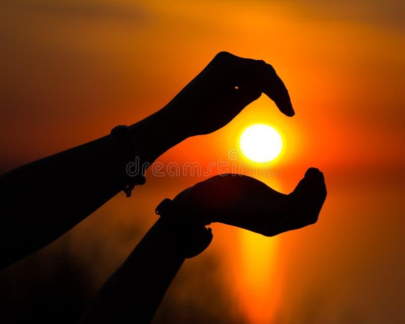 Esponga al sole la siluetta al tramonto concentrato per beetween le mani immagine stock