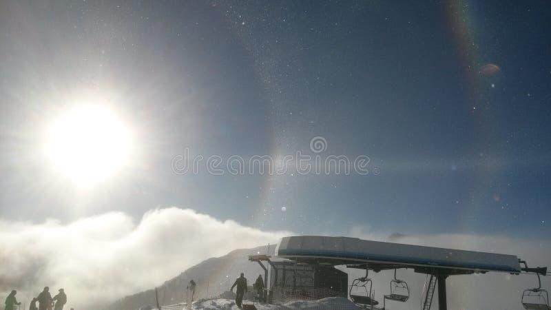 Esponga al sole sopra le alpi in Italia durante il giorno soleggiato con l'arcobaleno fotografia stock