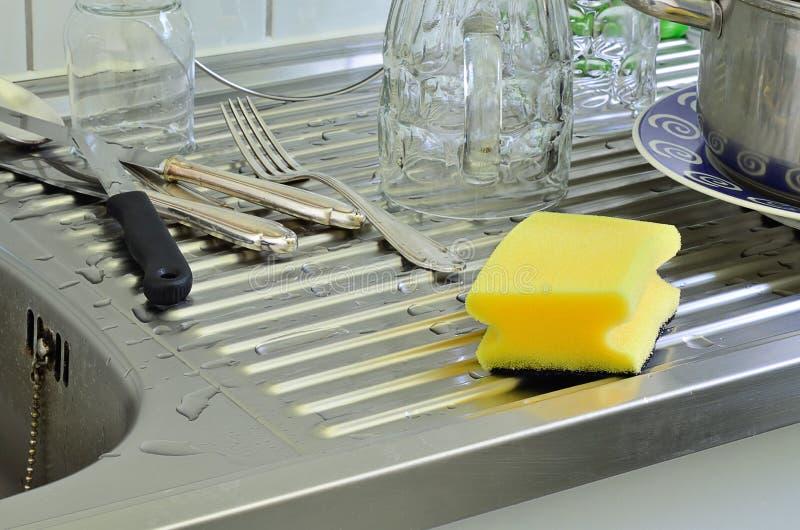 Esponja amarilla de la limpieza con los vidrios, los platos y Curtley fotos de archivo libres de regalías