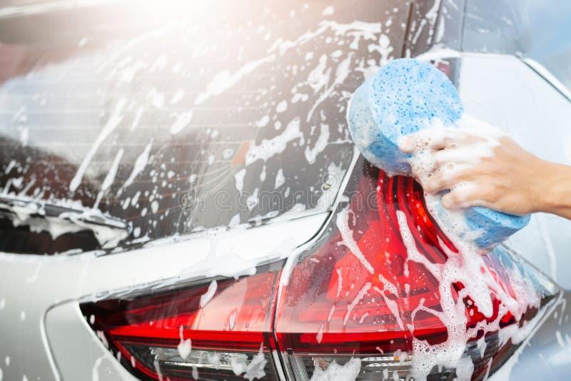 Esponja azul da mão da terra arrendada do trabalhador do homem dos povos para o carro de lavagem imagem de stock royalty free