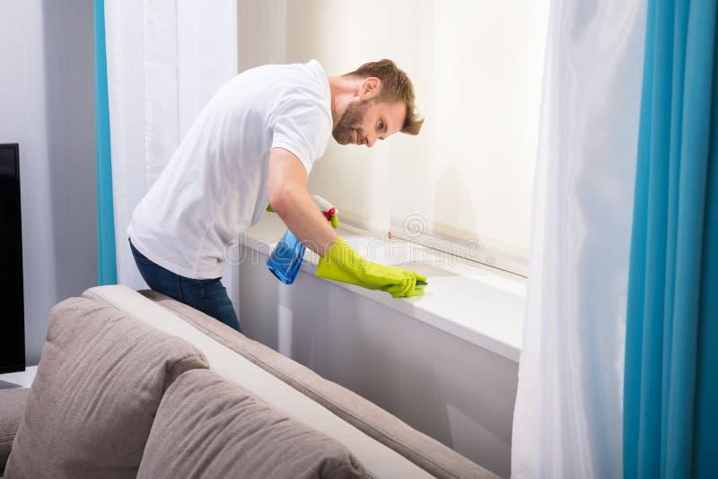 Esponja de Cleaning Windowsill With do guarda de serviço fotografia de stock royalty free