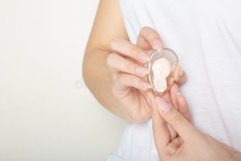 Esponja transparente del silicón de la tenencia de la mano de la mujer con crema del bb Copie el espacio fotografía de archivo