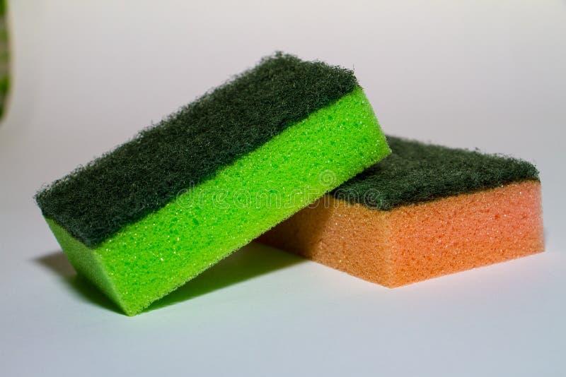esponja verde sobre esponja anaranjada imagen de archivo