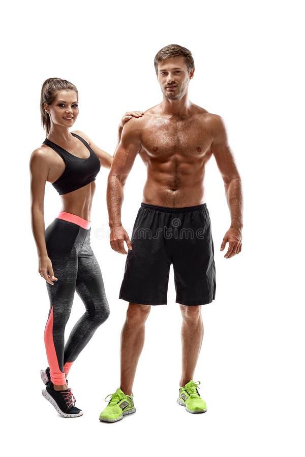 Esporte, aptidão, conceito do exercício Pares aptos, homem muscular forte e mulher magro levantando em um fundo branco imagem de stock