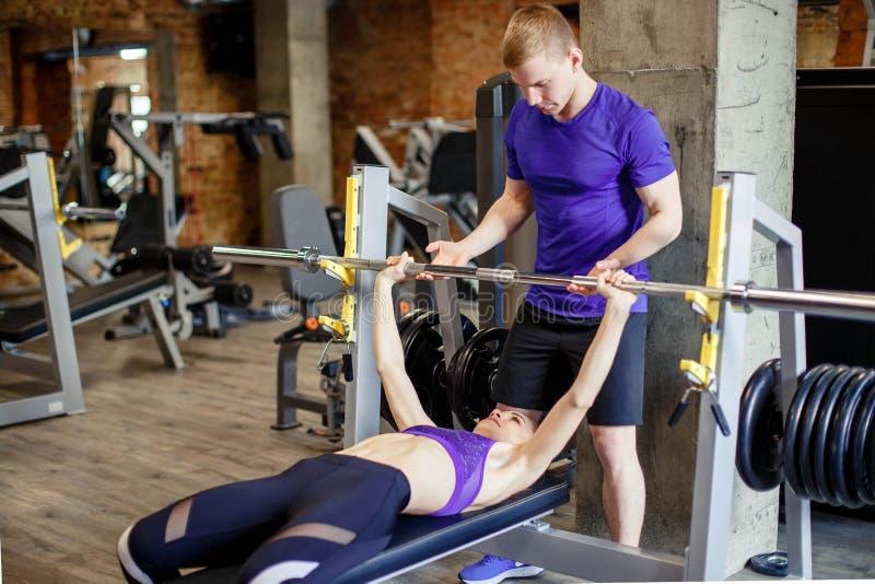 Esporte, aptidão, halterofilismo e conceito dos povos - a mulher e o instrutor pessoal com barbell barram o dobramento dos múscul imagem de stock royalty free