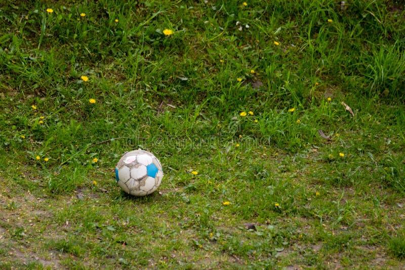 esporte Bola de futebol suja velha na grama Futebol imagens de stock royalty free
