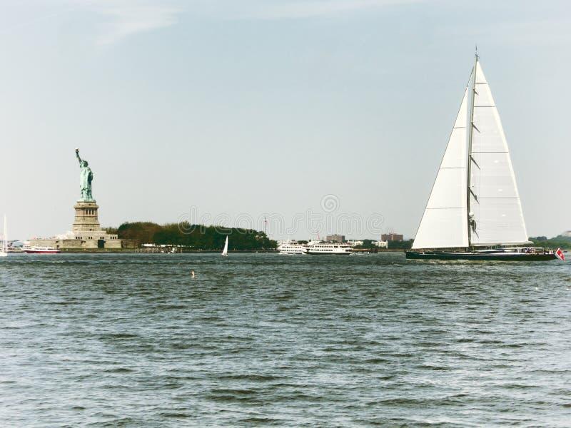 Esporte de barco de Sailingboat perto da estátua da liberdade imagens de stock