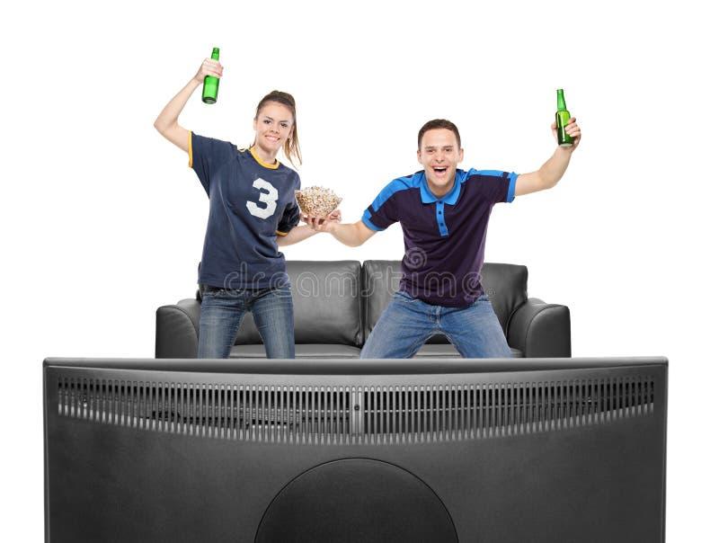 Esporte de observação Excited do menino e da menina em uma tevê imagem de stock royalty free