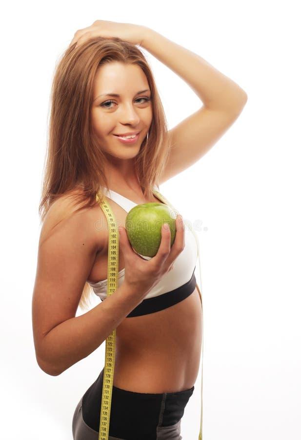 Esporte, dieta, saúde e conceito dos povos: A mulher alegre nova nos esportes veste com a maçã, isolada sobre o fundo branco imagens de stock royalty free