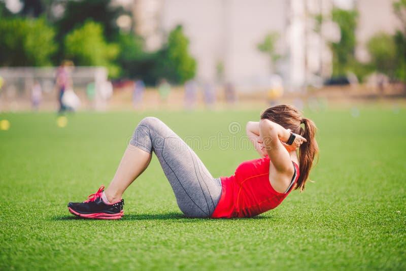 Esporte e saúde do tema A mulher caucasiano bonita nova que faz o aquecimento, aquecendo os músculos, os músculos abdominais malh foto de stock