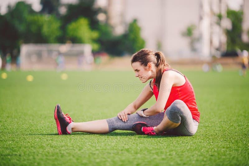 Esporte e saúde do tema Mulher caucasiano bonita nova que senta-se fazendo o aquecimento, aquecendo os músculos, esticando a gram imagens de stock royalty free