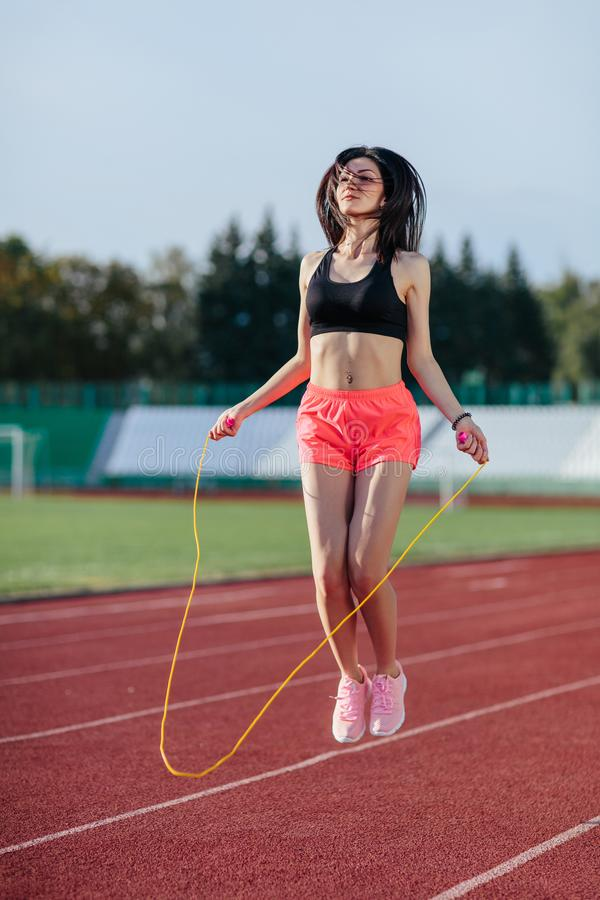 Esporte, exerc?cios fora a mulher na parte superior preta e aumentou short que salta na corda de salto no estádio Menina desporti imagens de stock