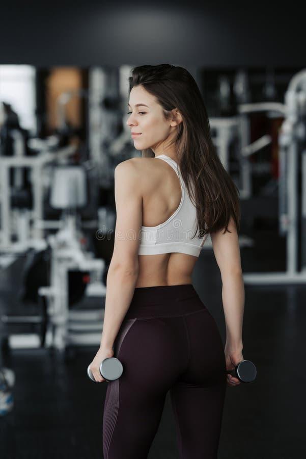 esporte A mulher atl?tica da aptid?o que bombeia acima muscles com pesos Menina 'sexy' moreno da aptidão no desgaste do esporte c fotografia de stock