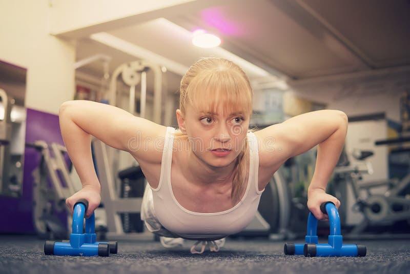 esporte Mulher bonita no gym, louro bonito bonito ao fazer impulso-UPS em um simulador especial da flexão de braço, crossfit foto de stock royalty free