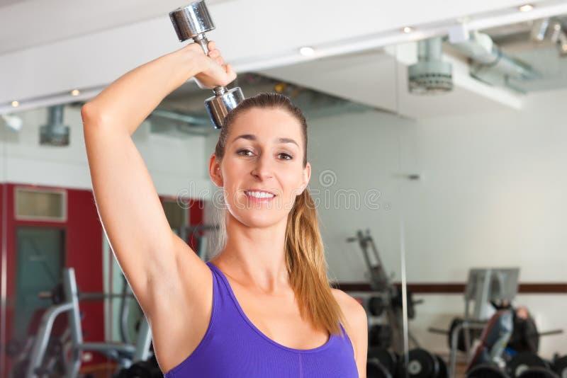 Esporte - a mulher está exercitando com o barbell na ginástica foto de stock royalty free