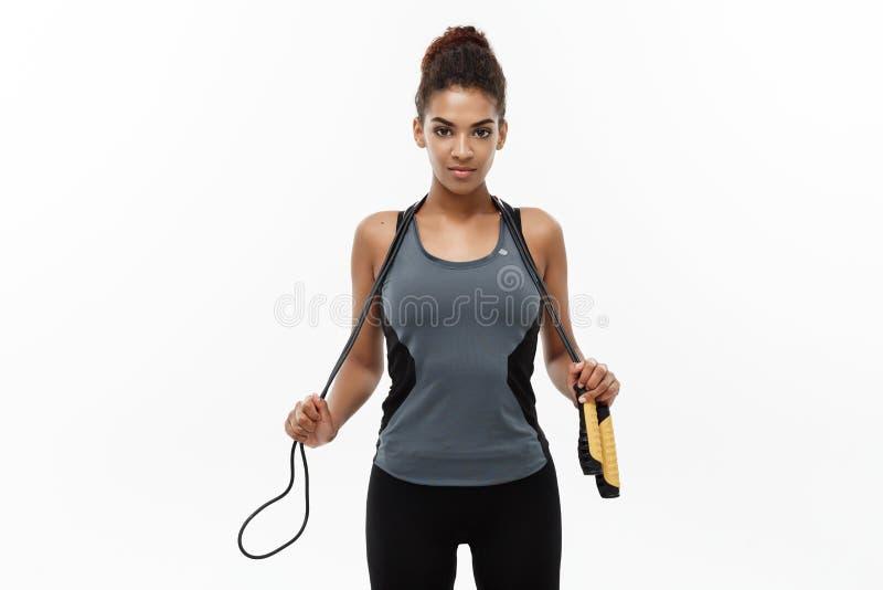 Esporte, treinamento, estilo de vida e conceito da aptidão - retrato da mulher afro-americano feliz bonita que exercita com fotografia de stock royalty free