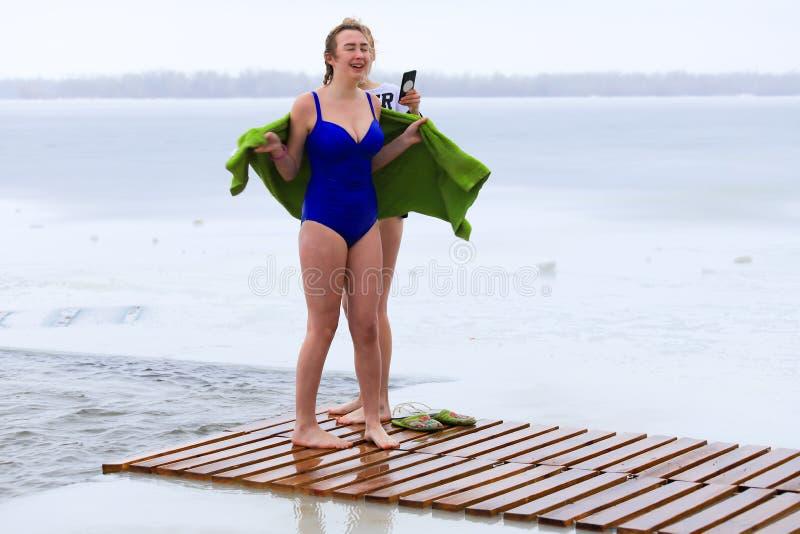 Esportes de inverno, endurecimento As mulheres ficam no inverno perto do buraco de gelo no rio Dnieper durante o feriado ortodoxo imagens de stock royalty free